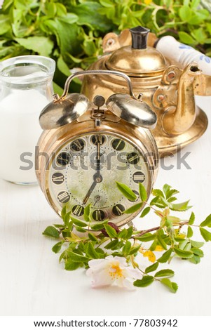 Old alarm-clock, teapot and jug of milk with wild flowers on white table - stock photo