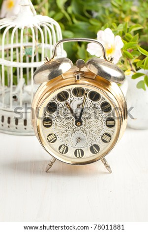 Old alarm-clock, vintage cage and wild rose on white table - stock photo