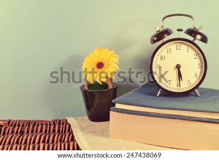 Old alarm clock with  books and yellow flower  vase on wood basket texture - stock photo