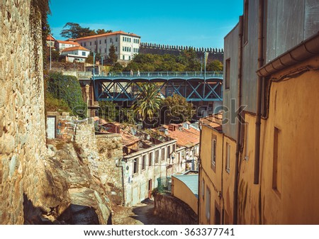 Old alley in Porto with a bridge in the background. - stock photo