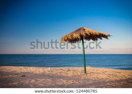 Old alone umbrella on the beach, sunny day at resort