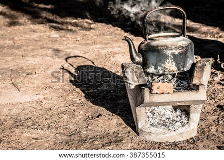 old aluminium kettle on stove.people is boiling water at the countryside in the sunset morning - stock photo