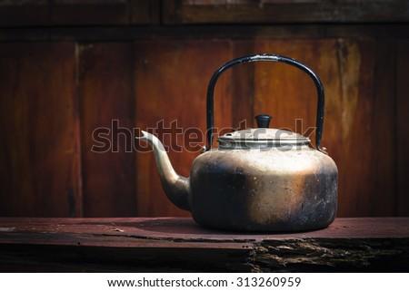 Old aluminium kettle on wood background in vintage - stock photo