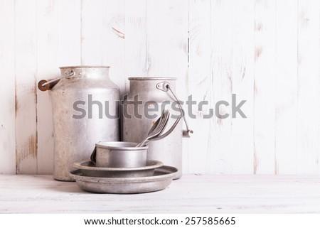 Old aluminium utensils on the shabby chic kitchen - stock photo