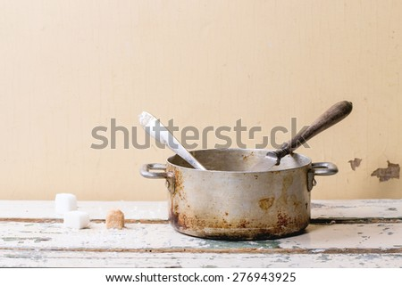 Old aluminum pan of homemade caramel sauce, served with spoons and sugar cubes over white wooden table. - stock photo