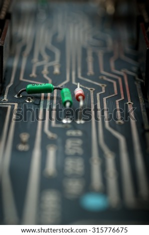 Old analog PCB in a dark colors with electronic components. Close up with extremely shallow DOF. - stock photo