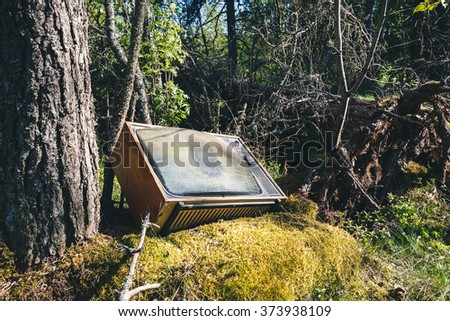 Old analog television in forest - stock photo