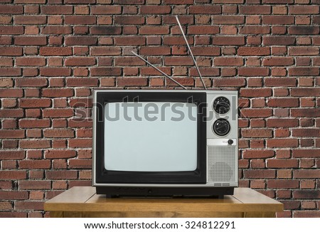 Old analogue television on wood table with brick wall. - stock photo