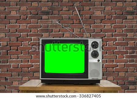 Old analogue television with chroma key green screen and brick wall.