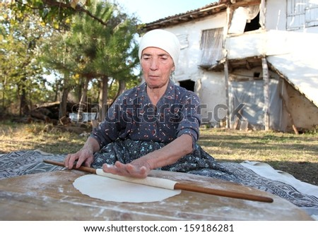 Old Anatolian (Turkish) woman is rolling out the paste