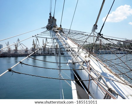 Old Ancient sailboat. The historic three-masted sailing ship without sails docked in the harbor waterfront. - stock photo