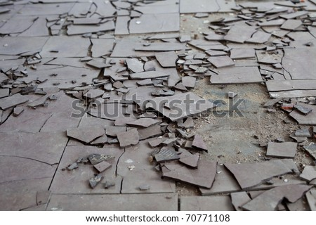 Old and broken asbestos floor tiles - stock photo