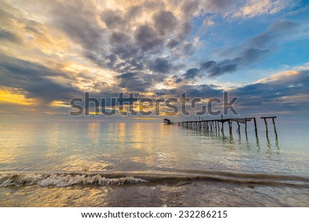 Old and damaged wooden jetty with romantic colorful cloudscape at dusk on the coastline of Sulawesi, Indonesia. Sense of absence or failure. Wide angle shot, long exposure, blurred motion. - stock photo