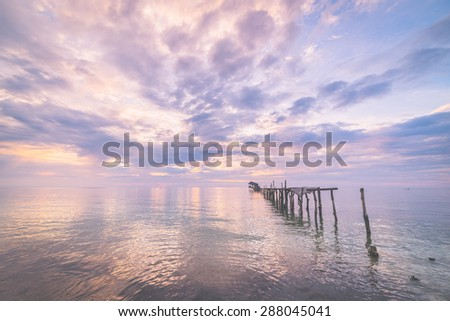 Old and damaged wooden jetty with romantic colorful cloudscape at dusk on the coastline of Sulawesi, Indonesia. Wide angle shot, long exposure, blurred motion. Marsala toned image, vignetting added.  - stock photo
