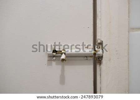 Old and decayed slide lock with shadow on a dirty white door - stock photo