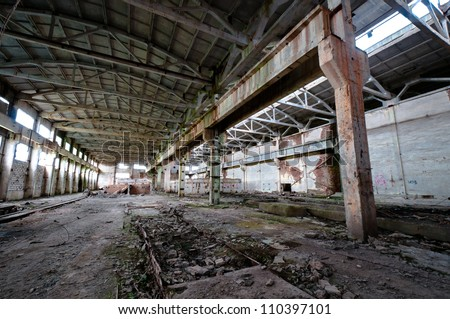 Old and deserted plant interior with weathered walls and overlap - stock photo