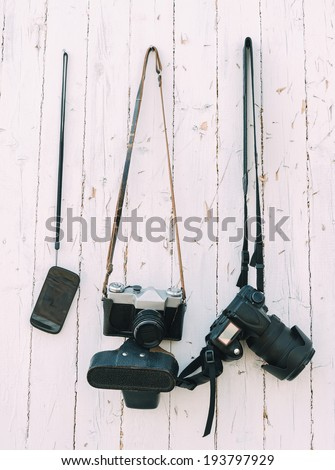 Old and digital photo cameras are hanging on the wooden wall - stock photo