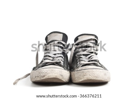 Old and dirty black canvas sneakers, isolated