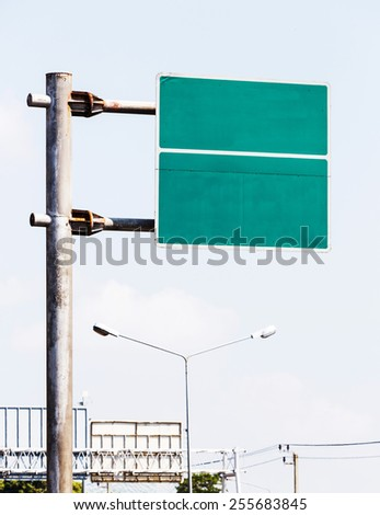 Old and dirty blank green color sign board on rusty pole in city - stock photo