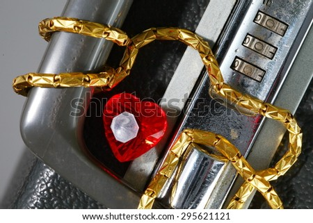 Old and dirty briefcase with gold necklace and plastic heart shape red color represent the business concept related idea.