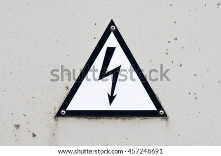 Old and dirty high voltage sign on white metal plate - stock photo