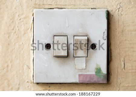 Old and dirty Light control switch on yellow background - stock photo
