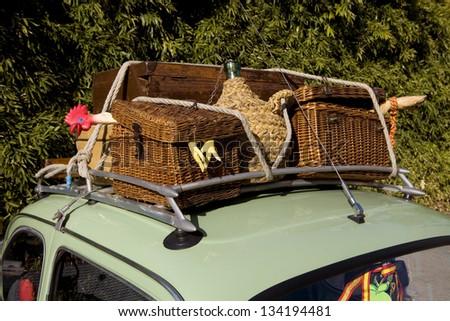 Old and funny wicker suitcases. Funny vintage baggage on the roof of an old car - stock photo