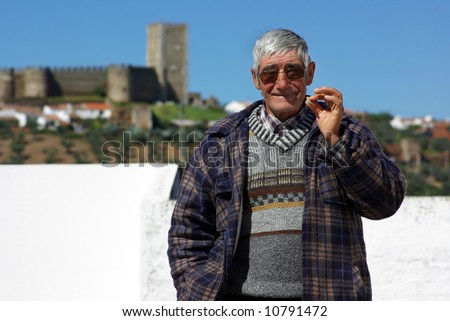Old and happy man smokes a cigarette. - stock photo