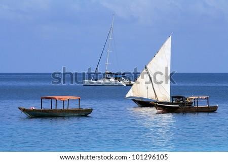 Old and modern boats in Zanzibar in a sunny day - stock photo