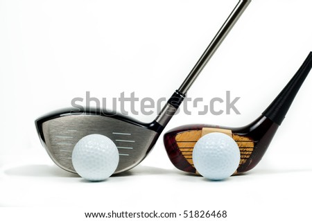 Old and new golf drivers beside one another iwth golf balls - stock photo