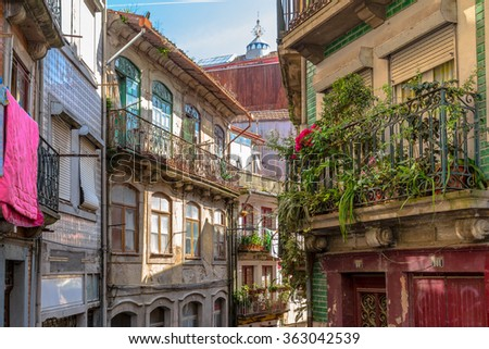 Old and ruined alley decorated with plants in downtown Porto. - stock photo