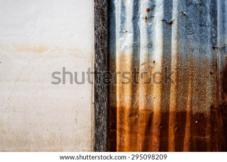 Old and Rusted decay metal sheet wall with wood fram and cement wall - stock photo