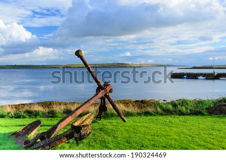 old and rusty anchor from warship on shore - stock photo - stock photo