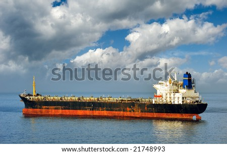 Old and rusty bulk carrier cargo ship laying empty, due to state of world economy - stock photo