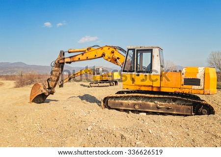 Old and rusty excavating machines digging out pebbles from the bank of the river, one excavator's arm framing the other. - stock photo