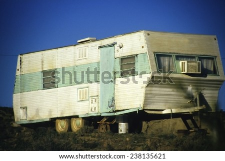 Old and rusty green and white motor home - stock photo