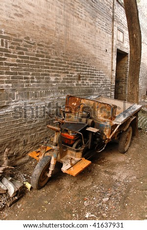Old and rusty scratch-built Frankenstein cargo bike on the street of Chinese village.