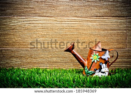 old and rusty watering can on green grass with wood background - stock photo