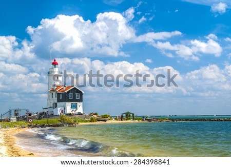 Old and small Lighthouse in seaside with nice beach and clouds. (North Holland) - stock photo