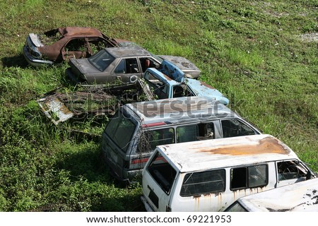 Old and unwanted cars and vans rot on some wasteland.  The cars will probably be scrapped. - stock photo