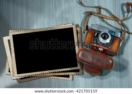 Old and vintage camera with leather case and a stack of photo frames on a desk with shadows - stock photo