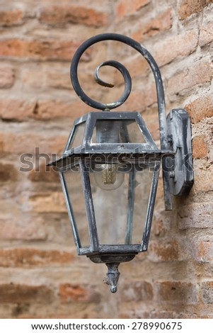 Old and vintage electric lamp on brick wall - stock photo