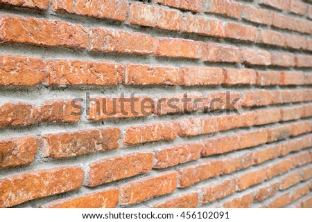 Old and vintage orange brick wall - weathered and worn out in outdoor area - perspective view - stock photo
