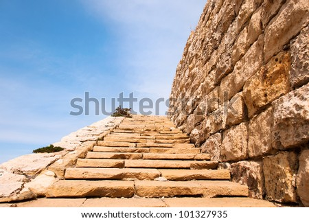 Old and weather-worn limestone steps leading up to nowhere, seemingly reaching to the sky. - stock photo