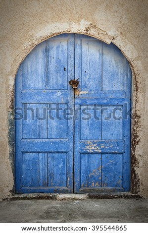 Old and weathered blue door to a property in Oia on the greek island of Santorini - stock photo