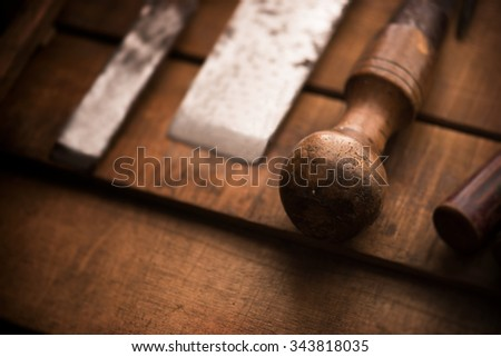 Old and well used wood carving chisels, prepared on a old workbench. Old chisel with an oak handle. Shallow depth of field. Low key. - stock photo