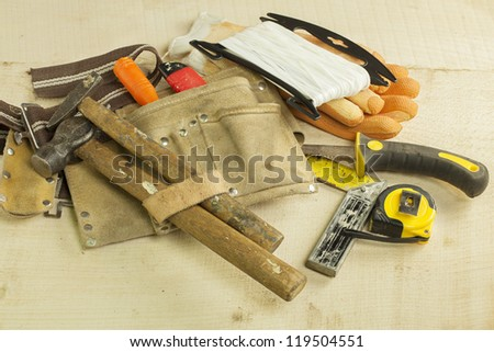 Old and worn carpentry tools placed on wooden planks - stock photo