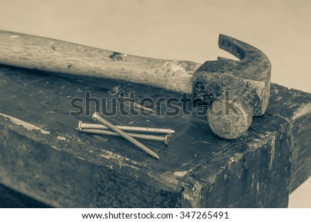 Old and worn contracting hammer and three nails on a distressed work bench - stock photo