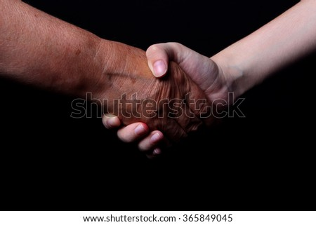 old and young hands are shaking hands on a black background - stock photo