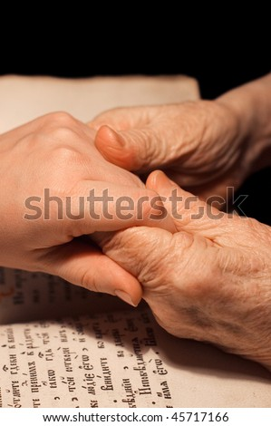 Old and young hands on the bible - stock photo